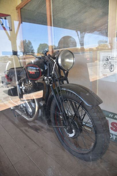 An old BSA motorcycle in an old shop window.